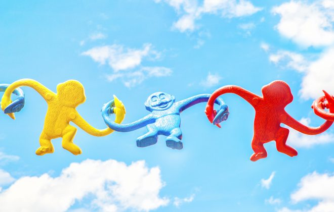 rubber monkeys holding one another in what's effective teamwork is about